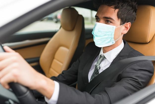 Uomo mascherato che guida la sua auto