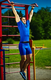 Uomo maschio dell'atleta felice sano sano bello che si esercita al parco della città - concetti di forma fisica un bello giorno di estate sulla barra orizzontale
