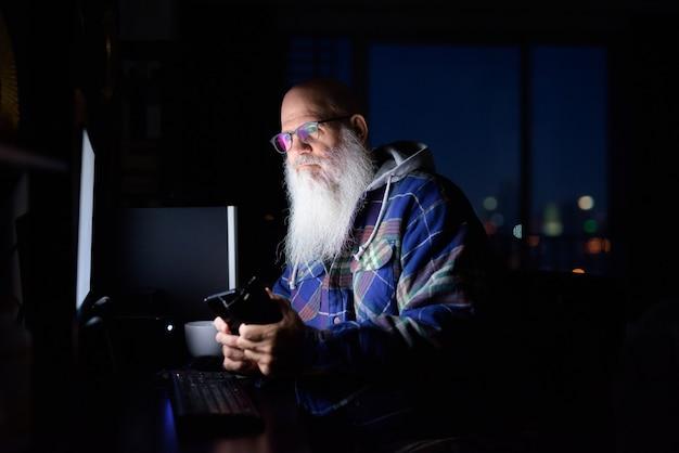 Uomo maturo calvo barbuto hipster pensando e utilizzando il telefono a casa a tarda notte al buio