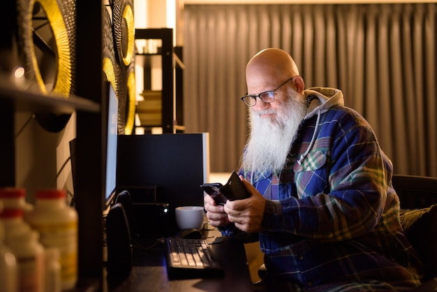 Uomo maturo calvo barbuto hipster utilizzando il telefono mentre si fa lo straordinario a casa a tarda notte