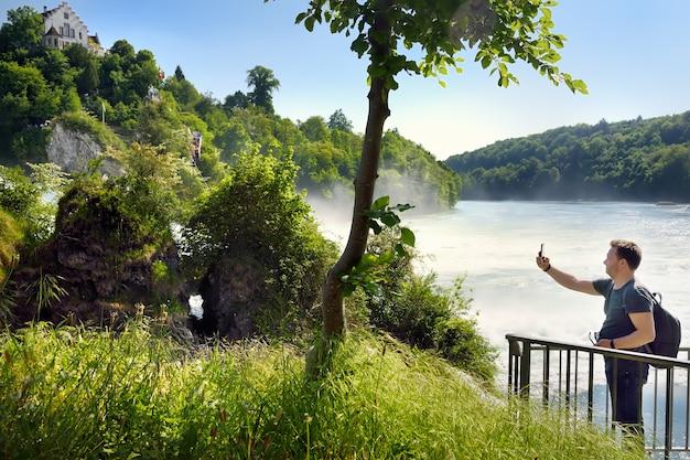Uomo maturo che cattura una foto delle cascate del reno, svizzera