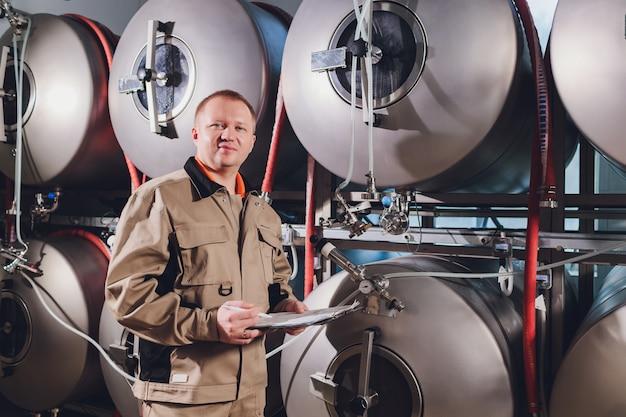 Uomo maturo che esamina la qualità della birra artigianale al birrificio. ispettore che lavora nella fabbrica di produzione di alcol che controlla birra. uomo in distilleria che controlla controllo di qualità della birra alla spina.