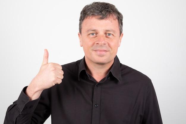 Uomo maturo che gesturing il segno giusto sfoglia su