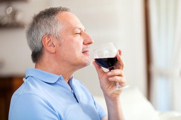 Uomo maturo che gode un bicchiere di vino rosso
