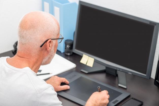 Uomo maturo che lavora alla sua tavoletta grafica