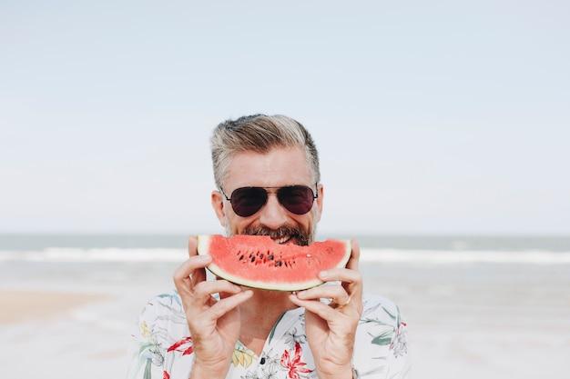 Uomo maturo che mangia anguria in spiaggia