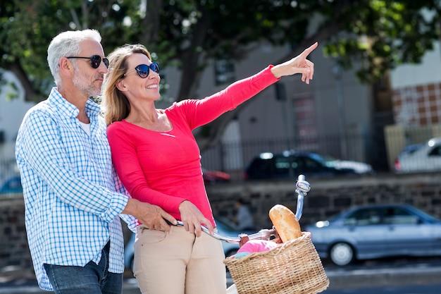 Uomo maturo con la donna che indica nella città
