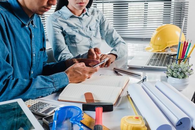 Uomo maturo dell'ingegnere dell'architetto che per mezzo di uno smartphone discute le informazioni con un collega più giovane.