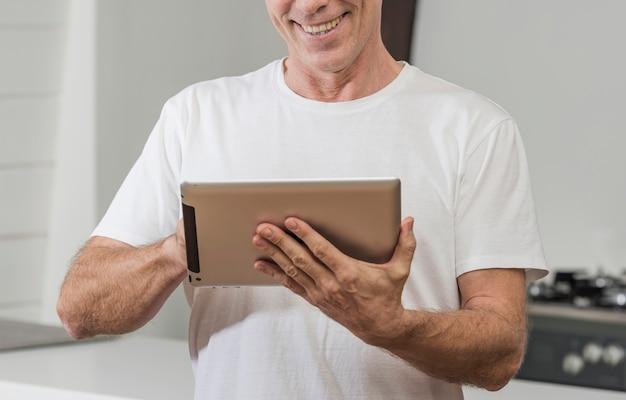 Uomo maturo di smiley che per mezzo di una compressa