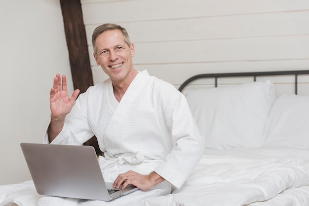 Uomo maturo di smiley che tiene un computer portatile a letto con lo spazio della copia