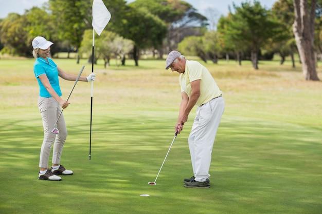 Uomo maturo e donna che giocano a golf
