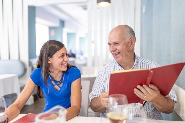 Uomo maturo e giovane donna che godono e che sorridono, trascorrendo del tempo insieme