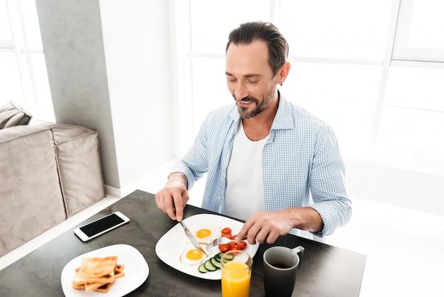 Uomo maturo felice che mangia prima colazione sana saporita