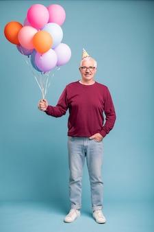 Uomo maturo felice in protezione di compleanno e abbigliamento casual che tiene palloncini mentre posa sulla parete blu