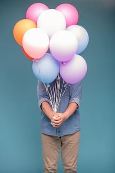 Uomo maturo in abbigliamento casual tenendo un mazzo di palloncini colorati mentre si sta in piedi in isolamento