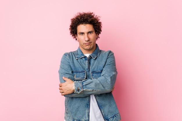 Uomo maturo riccio che indossa una giacca di jeans su sfondo rosa accigliato in disappunto, tiene le braccia conserte.