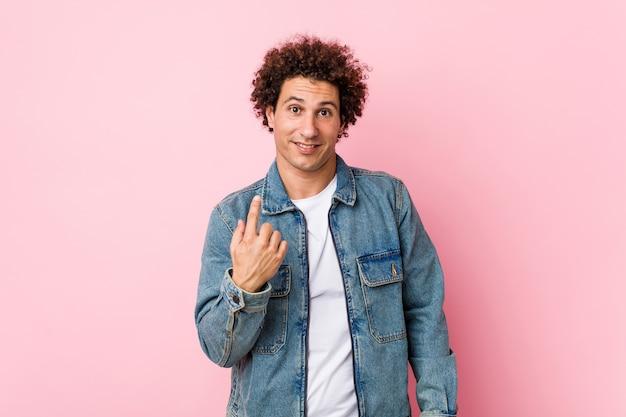 Uomo maturo riccio che indossa una giacca di jeans su sfondo rosa che punta il dito contro di te come se invitando ad avvicinarsi.