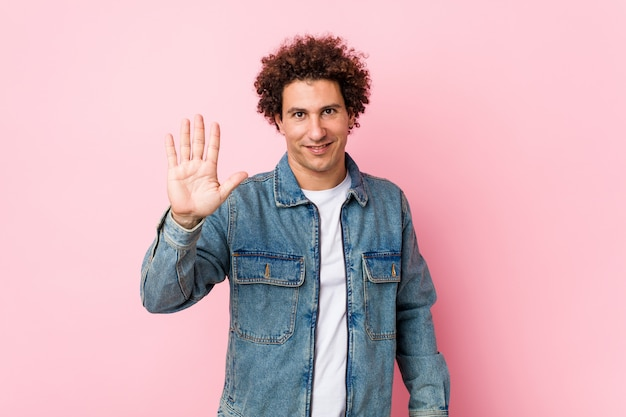 Uomo maturo riccio che indossa una giacca di jeans su sfondo rosa sorridente mostrando allegro numero cinque con le dita.
