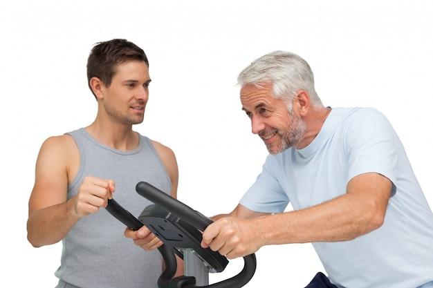Uomo maturo risoluto sulla bici fissa con l'istruttore