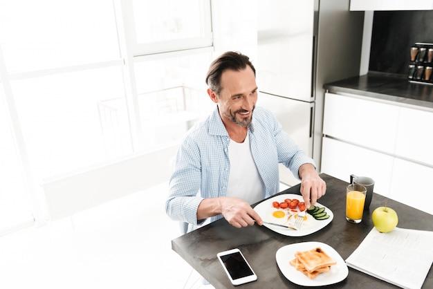 Uomo maturo sorridente che mangia prima colazione sana saporita