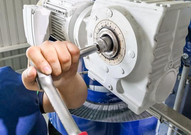 Uomo meccanico che utilizza una chiave per riparare o mantenere il motore di azionamento sulla macchina