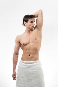 Uomo medio del colpo che propone in telo da bagno
