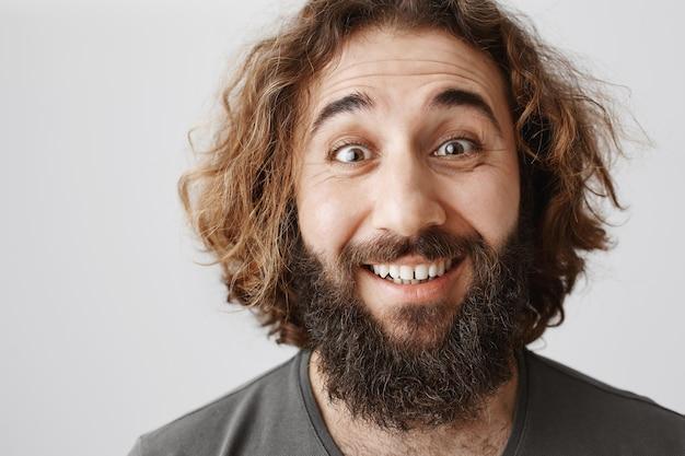 Uomo mediorientale felice eccitato con la barba che sembra gioioso, sorridente entusiasta