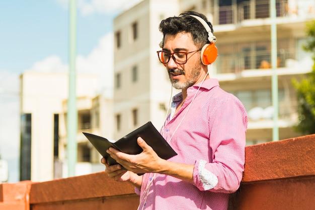 Uomo moderno che sta contro la musica d'ascolto della parete sul libro di lettura della cuffia
