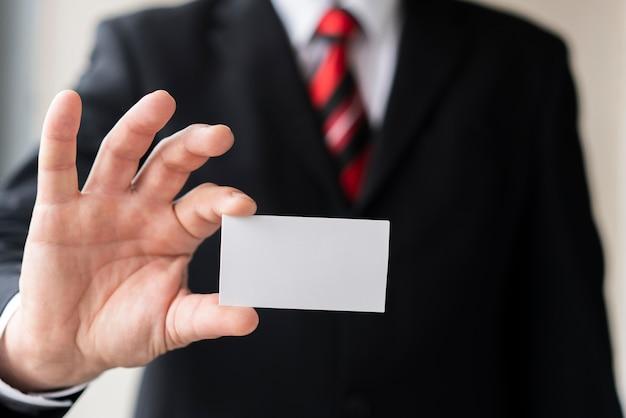Uomo moderno che tiene biglietto da visita in bianco
