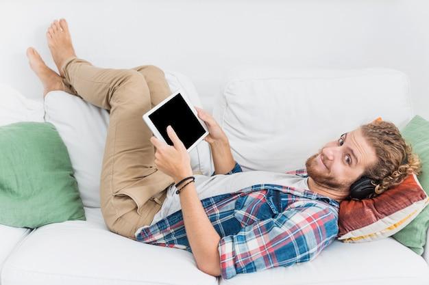 Uomo moderno che utilizza la tabella sul divano