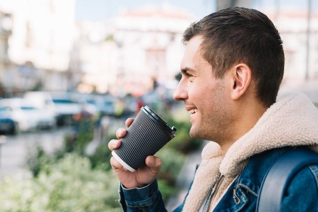 Uomo moderno con la tazza di caffè in ambiente urbano