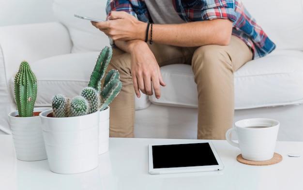 Uomo moderno con smartphone sul divano