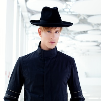 Uomo moderno di moda nero far west nero con cappello in interni moderni