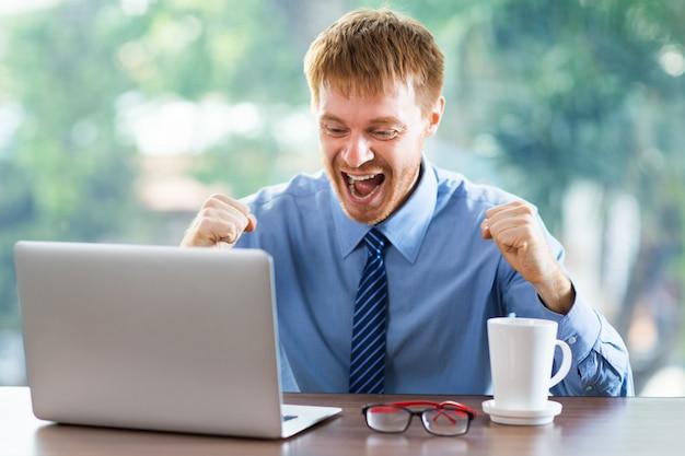 Uomo molto felice che celebra con i pugni su alta qualcosa che vede sul suo computer portatile