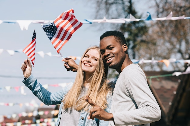 Uomo multietnico e donna con bandiere americane