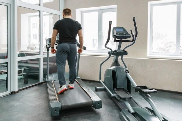 Uomo muscolare atletico che funziona sui tapis roulant