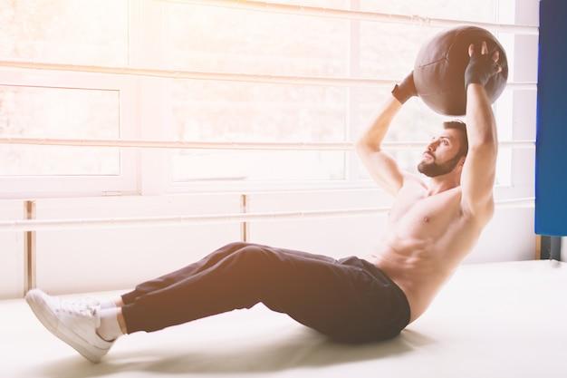 Uomo muscolare bello che fa sit-up su un pavimento di legno.