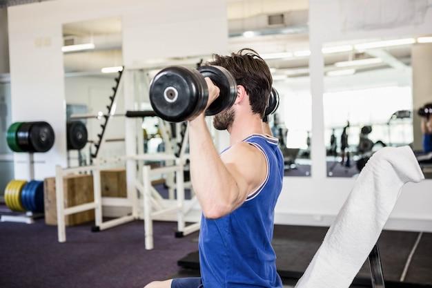 Uomo muscolare che alza i dumbbells sul banco in palestra