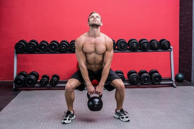 Uomo muscolare che alza un kettlebell