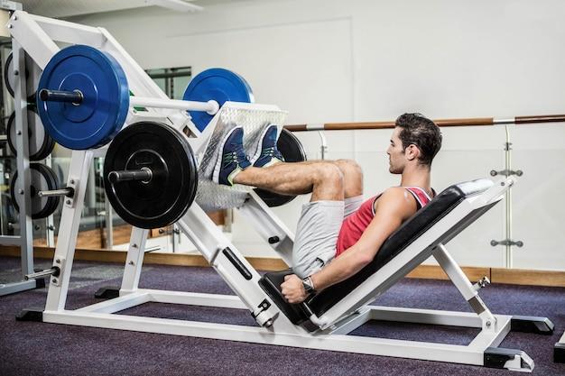 Uomo muscolare che fa esercizio per le gambe in palestra