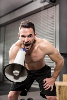 Uomo muscolare che grida sul megafono nella palestra di crossfit