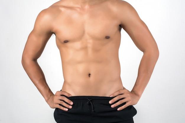 Uomo muscolare che mostra sei addominali del pacchetto isolati su fondo bianco.