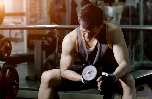 Uomo muscolare che risolve con le teste di legno