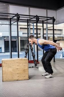 Uomo muscolare che salta sul blocco di legno presso la palestra di crossfit