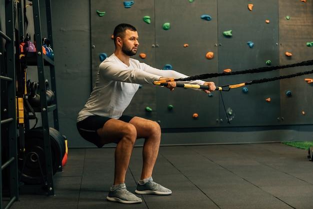 Uomo muscolare che si esercita nel centro benessere o in palestra. usando le aste, facendo flessioni e rotazioni del busto con le gambe sospese. concetto di fitness, sport, allenamento, allenamento e stile di vita.