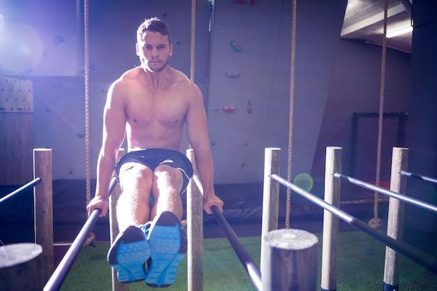 Uomo muscolare che si esercita su barre parallele
