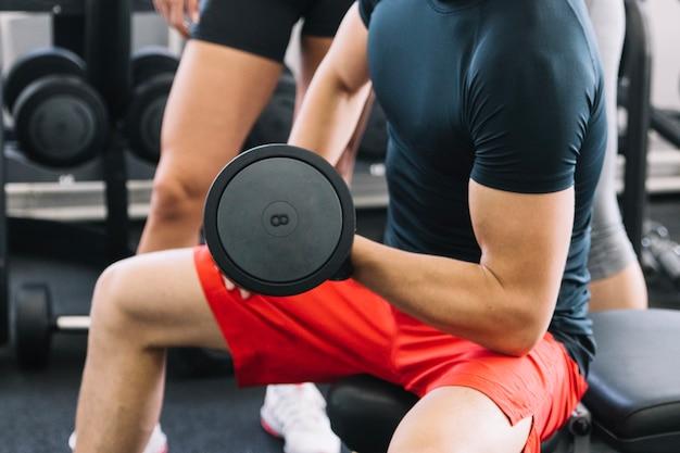 Uomo muscolare che tiene dumbbell