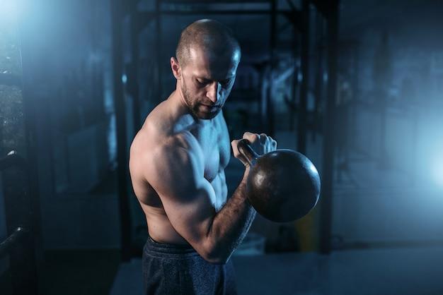 Uomo muscolare esercizi con kettlebell sull'allenamento in palestra. forte allenamento atleta con il peso