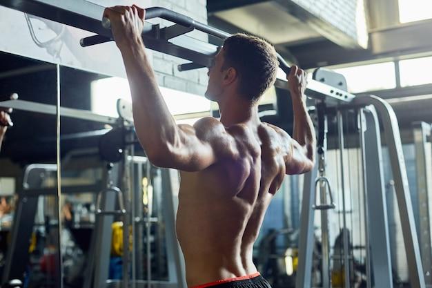 Uomo muscolare nudo che risolve in palestra