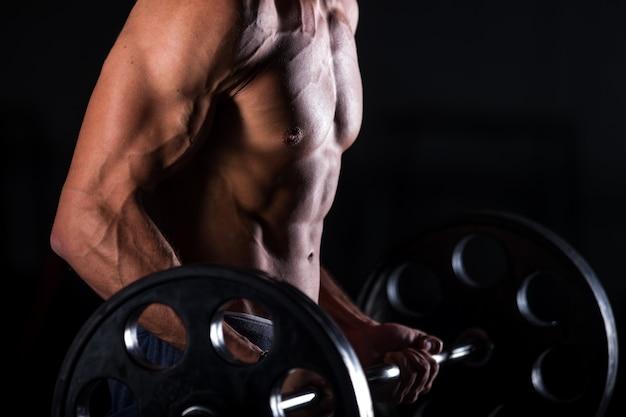 Uomo muscolare sollevando un bilanciere nel centro fitness